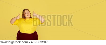 Thumbs Up, Flyer. Beautiful Plump Caucasian Plus Size Model Isolated On Yellow Studio Background. Co