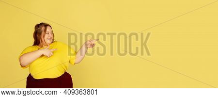 Pointing At Side, Flyer. Beautiful Plump Caucasian Plus Size Model Isolated On Yellow Studio Backgro