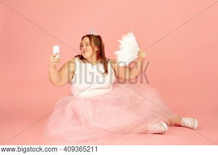 Selfie. Beautiful Plump Caucasian Plus Size Model In Fairys Outfit Isolated On Pink Studio Backgroun