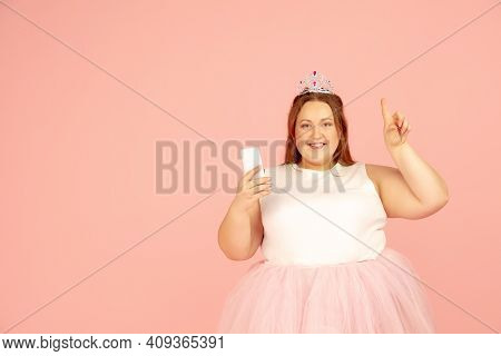 Pointing. Beautiful Plump Caucasian Plus Size Model In Fairys Outfit Isolated On Pink Studio Backgro