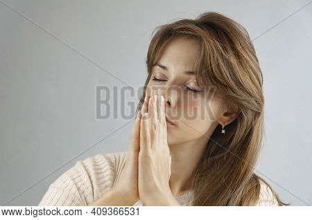 Concentrated Brunette Woman Praying At Home. Meditative Concept.