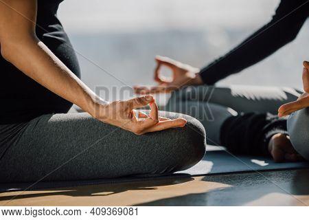 Close Up Of Two Woman Sitting Cross-legged In Padmasana, Lotus Posture, Yoga Hands Pose, Focus On Fi