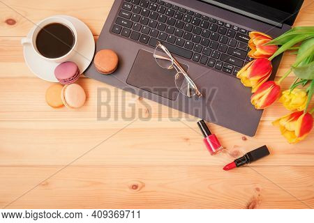 Laptop Keyboard, Coffee Cup, Glasses, Lipstick, Nail Polish And  Tulip Flowers On Wooden Table. Top