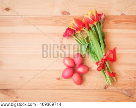 Red Easter Eggs And Tulip Flowers With Red Ribbon On Wooden Background. Top View, Copy Space.