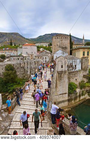 MOSTAR, BOSNIA AND HERZEGOVINA - SEPTEMBER 05: People walking on Old Bridge on September 05, 2015 in Mostar, Bosnia and Herzegovina.