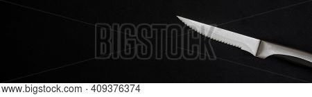 Sharp Stainless Steel Self-sharpening Knife On A Black Background. Serrated. For Cutting Laminated A