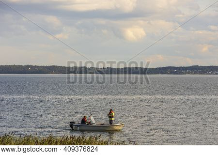 Beautiful Baltic Sea Landscape View. Men Fishing From Motorboat. Water Surface Merging With Coast Li