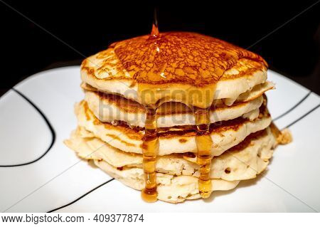 Maple Syrup Pouring Onto Fluffy Hotcakes On A White Plate Against A Black Background.