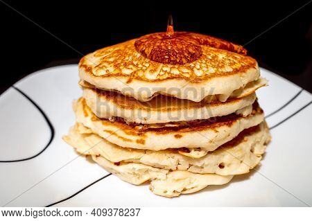 Close Up Of Maple Syrup Pouring Onto Fluffy Hotcakes On A White Plate With A Black Background.
