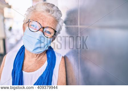Elder senior woman with grey hair wearing coronavirus safety mask leaning on the wall outdoors