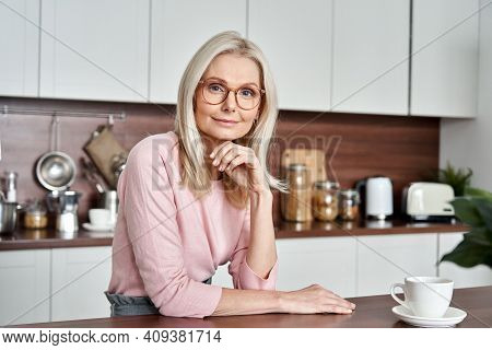 Happy Mature Middle Aged 50s Woman Wearing Glasses Sitting At The Kitchen Table. Smiling Older Adult