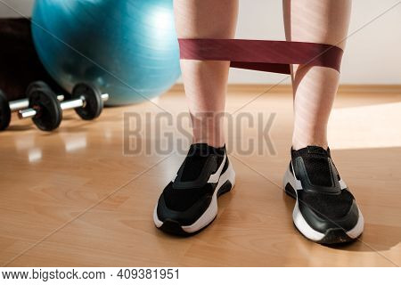 Female Legs In Sports Leggings And Sneakers Doing Exercises With Fitness Elastic Bands At Home Durin