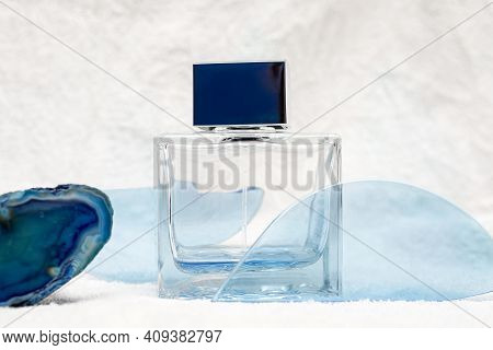 Glass Bottle For Men Perfume Or Aftershave Among Abstract Blue Drifts On Snow White Background. Refr