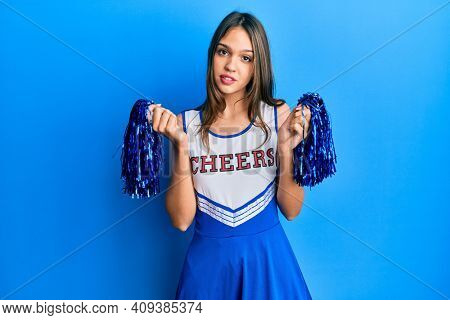 Young brunette woman wearing cheerleader uniform relaxed with serious expression on face. simple and natural looking at the camera.