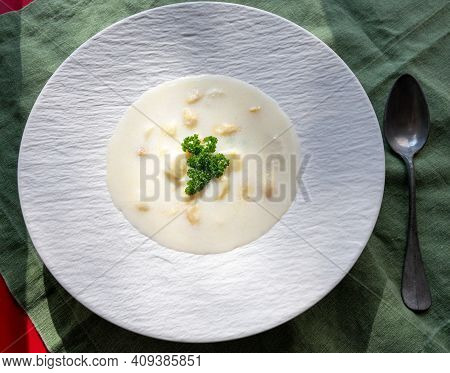 Homemade Fresh Seasonal White Asparagus Cream Soup In Sun Lights Close Up