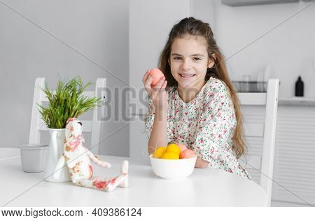 European Girl 10 Years Old In The Kitchen At The Table With Pink And Yellow Easter Eggs And A Toy Ra