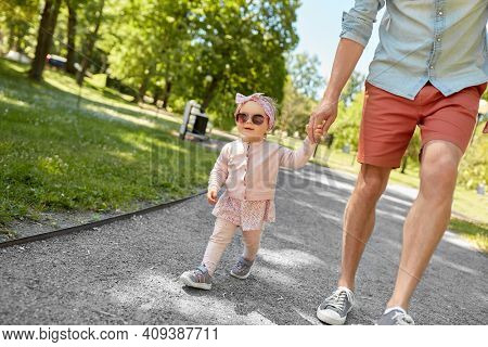family, fatherhood and people concept - father with baby daughter walking at summer park