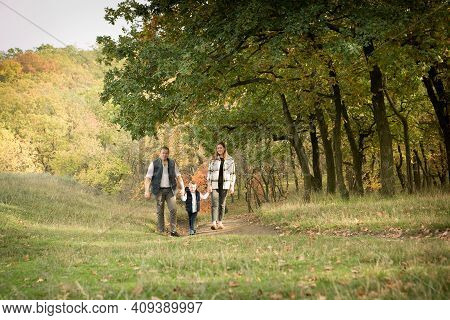 Fall. Close-up Of Happy Family On The Background Of The Autumn Forest. Happy Mom, Dad And Son Are Wa