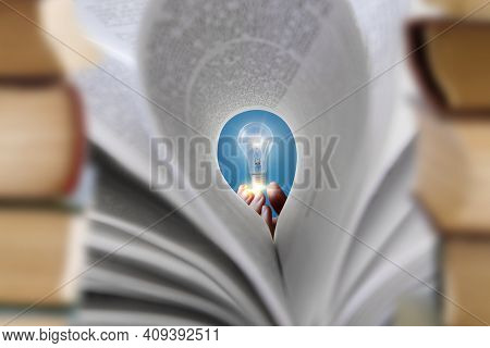The Concept Of Textbooks As A Source Of Ideas. Hand Holding A Hot Light Bulb In Front Of A Textbook.
