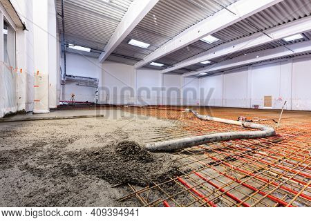 Concrete screed on floor heating in a new warehouse and office building. Interior finishing industry.