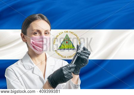 Girl Doctor Prepares Vaccination Against The Background Of The Nicaragua Flag. Vaccination Concept N