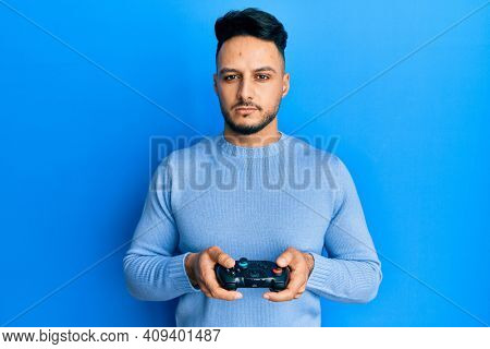 Young arab man playing video game holding controller relaxed with serious expression on face. simple and natural looking at the camera.