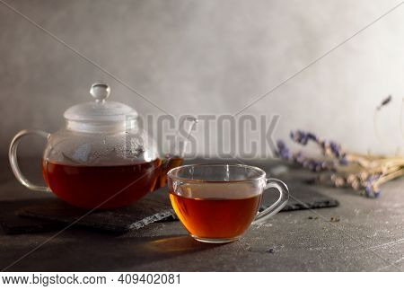 A Teapot And A Cup Of Tea On A Gray Concrete Background, The Teapot Stands On A Basalt Stand, Lavend