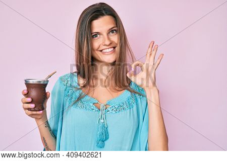 Beautiful caucasian woman drinking mate infusion doing ok sign with fingers, smiling friendly gesturing excellent symbol