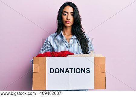 Beautiful hispanic woman volunteer holding donations box relaxed with serious expression on face. simple and natural looking at the camera.