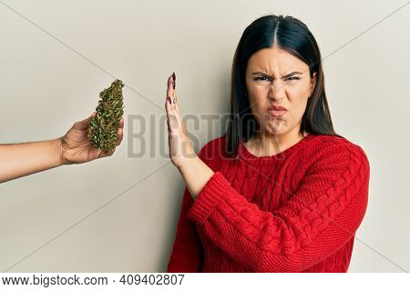 Beautiful brunette woman saying no to marijuana herb skeptic and nervous, frowning upset because of problem. negative person.