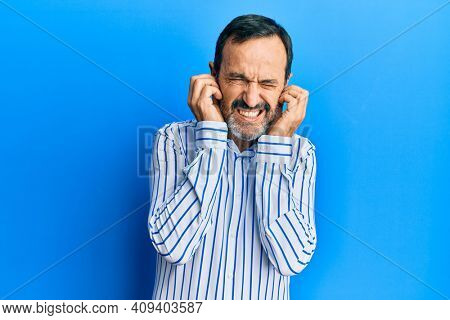 Middle age hispanic man wearing casual clothes covering ears with fingers with annoyed expression for the noise of loud music. deaf concept.