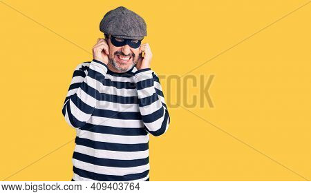 Middle age handsome man wearing burglar mask covering ears with fingers with annoyed expression for the noise of loud music. deaf concept.