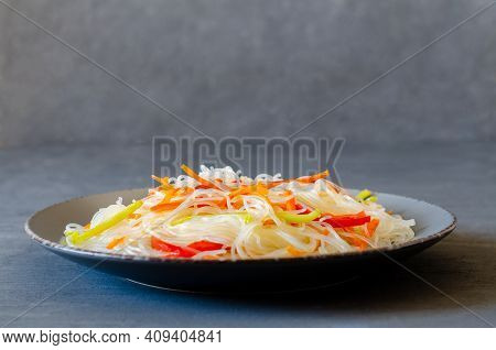 Asian Salad With Glass Noodles, Chicken And Vegetables On A Gray Background. Side View. Horizontal O
