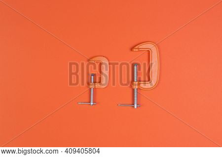 Clamp, Clamps On An Orange Background. Compress, Repair, Construction.
