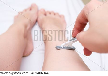 Woman Shaving Legs With A Grey Disposable Plastic Razor Close Up, Unwanted Hair Removing