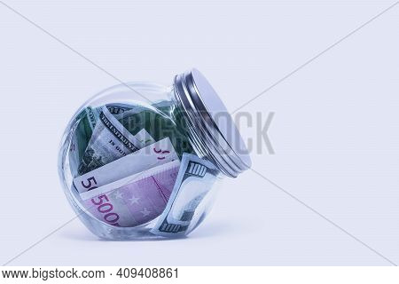 Glass Piggy Bank With Dollars And Euro On A White Background.