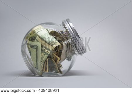 Glass Piggy Bank With Dollars And Euro On A Gray Background.