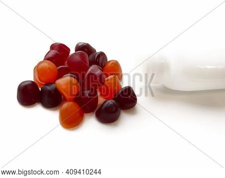 Group Of Red, Orange And Purple Multivitamin Gummies With The Bottle Isolated On White Background. H