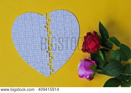 Jigsaw Puzzle The Shape Of A Heart Detached In The Middle With A Couple Of Roses