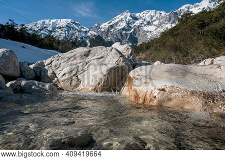 Clear Mountain River Flowing Over Rocks Through Evergreen Forest With Last Snow, Mieminger Plateau,