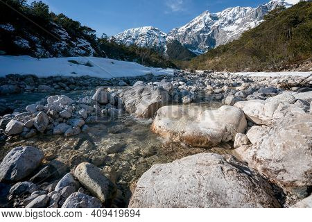Rocky Clear Mountain River Flowing Through Evergreen Forest With Last Snow, Mieminger Plateau, Tirol
