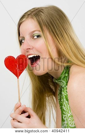 Young Woman Eating Heart Of Candy