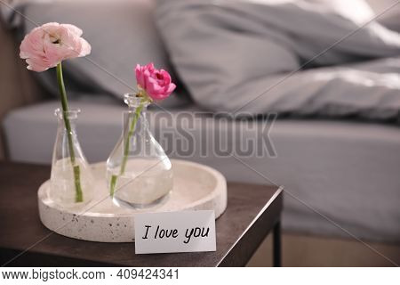 Note Saying I Love You Near Tray With Flowers On Bedside Table In Room
