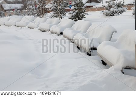 A Bench Blanketed With Snow In The Park. A Wooden Bench Covered With A Snow-white Blanket Of Snow. T