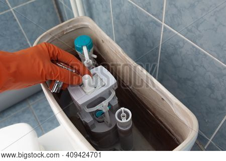 Toilet Tank Parts Replacement. A Man In Orange Gloves Repairs The Toilet Tank Drain.