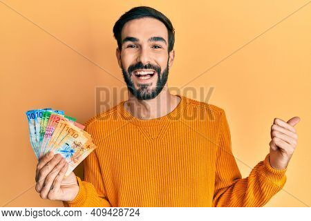 Young hispanic man holding swiss franc banknotes pointing thumb up to the side smiling happy with open mouth