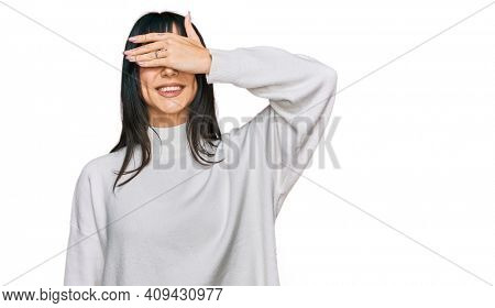 Young brunette woman with bangs wearing casual turtleneck sweater smiling and laughing with hand on face covering eyes for surprise. blind concept.