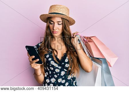 Young brunette woman holding shopping bags and smartphone relaxed with serious expression on face. simple and natural looking at the camera.