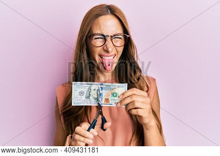 Young brunette woman cutting dollars with scissors for currency devaluation sticking tongue out happy with funny expression.