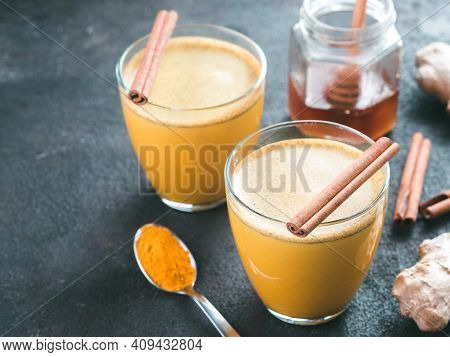 Healthy Drink Golden Turmeric Latte In Glass.gold Milk With Turmeric, Ginger Root, Cinnamon Sticks,